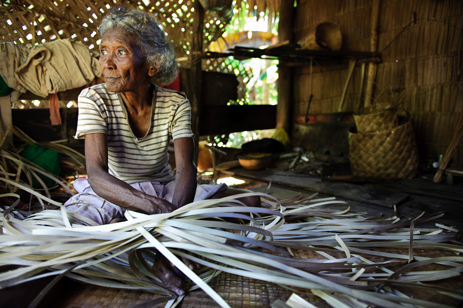 Mamanwa elder weaving a banig mat.
